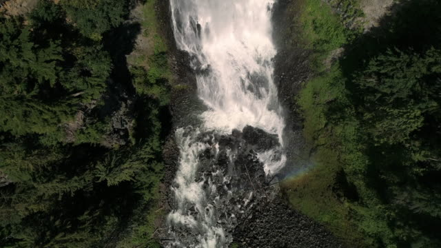 Slow Motion Drone Flying Up Waterfall with Overhead Perspective on Rainbow in Mist video