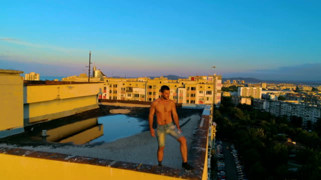 Slow motion drone shot of a man standing at the edge of a city building roof at sunset video