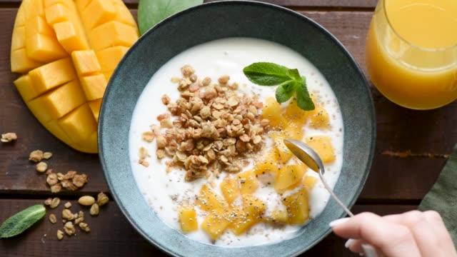 Slow motion eating yogurt with mango and granola