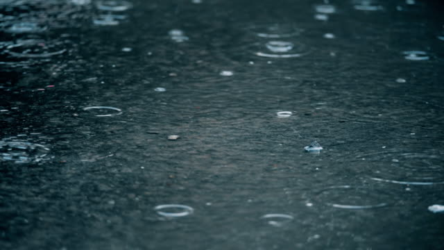 4K slow motion establishing shot of rain falling on pavement.