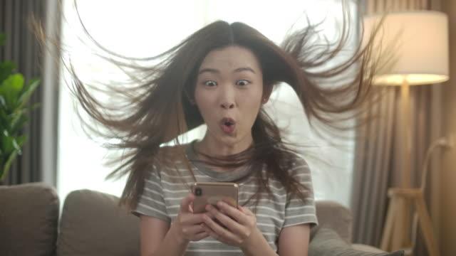 slow motion upphetsad asiatisk kvinna med smart telefon, telefon pristagare. goda nyheter flicka stansning luften - lotteri bildbanksvideor och videomaterial från bakom kulisserna