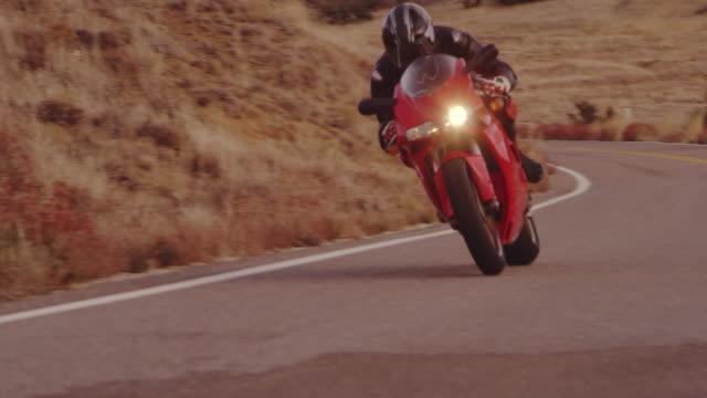vidéos et rushes de slow motion extrême motard moto sport à cheval sur la route de campagne rurale - moto sport