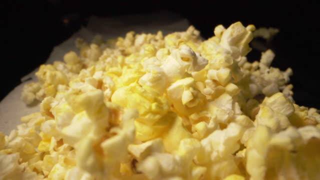 Slow Motion Falling Popcorn Close-Up Macro Wide Angle Heap of Fresh Buttery Greasy Yellow Popcorn on a Counter Top