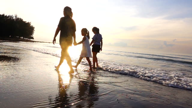 HD Slow motion: Family walk on a tropical beach at sunset