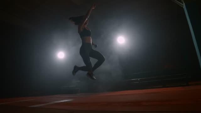 atleta femminile al rallentatore che esegue un salto in lungo durante una competizione. primo tempo - atletico video stock e b–roll