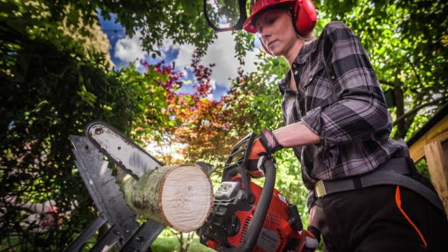 yavaş hareket: elektrikli testereyle odun kesen kadın işçi - şömine odunu stok videoları ve detay görüntü çekimi