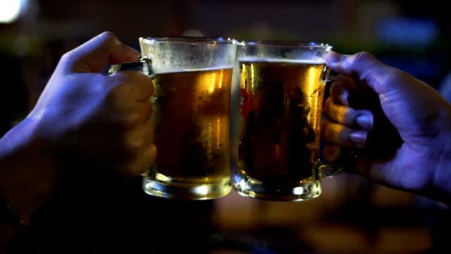 2 つのアジアのスローモーション fhd 映像男で一緒に応援して、ビールの乾杯と素晴らしく眼鏡バーとレストラン、リラックス、概念を飲む - グラス点の映像素材/bロール