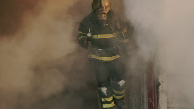 Slow motion fire fighter running towards the camera with fire in the background.
