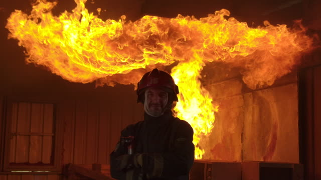 Slow motion fire fighter standing towards the camera with fire in the background.