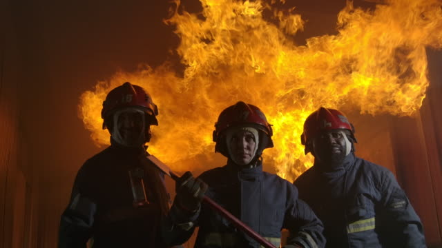 slow motion fire fighter standing towards the camera with fire in the background. - incendio doloso video stock e b–roll