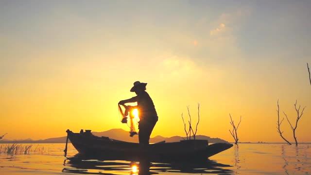 HD Slow motion: Fisherman on boat fishing at sunset