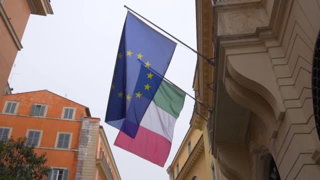 slow-motion. flagge der europäischen union und italien, auf dem gebäude im stadtzentrum von th - europäische union stock-videos und b-roll-filmmaterial