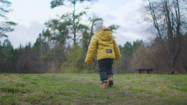 zeitlupe: einem jungen folgend, der in einem wald spazieren geht. ein kleiner junge läuft am sonnigen tag in einem bergwald spazieren. ein wanderer. kleiner junge 2-3 jahre alt in einer gelben jacke erkundet die natur und den wald - laub winter stock-videos und b-roll-filmmaterial