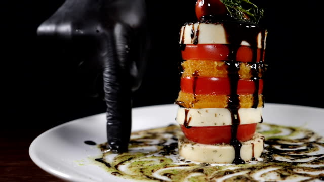 Slow motion food video concept. Salad Caprese on white plate poured with balsamic reduction. Sliced mozzarella, orange, tomato put one on another. Chef hand spreading sauce with finger on plate. Full hd