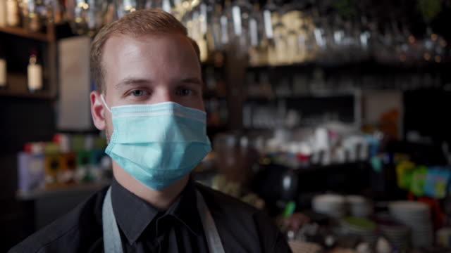 zeitlupenaufnahmen eines barkeepers mit schützender gesichtsmaske - bedienungspersonal stock-videos und b-roll-filmmaterial