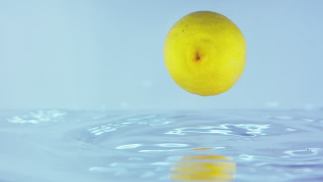 Slow Motion Footage Of A Lemon Falling And Rolling On Water Surface video