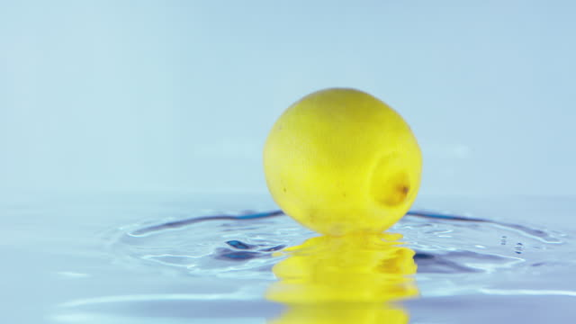 Slow Motion Footage Of A Lemon Falling On Water Surface video