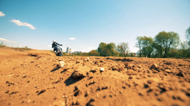 slow motion footage of a motorcycler riding across dusty terrain. slow motion - supercross video stock e b–roll