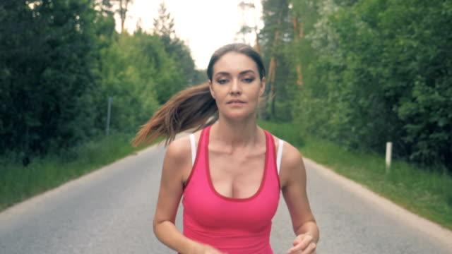 stockvideo's en b-roll-footage met slow motion beelden van een mooie dame joggen langs het steegje. gezond slank jonge sportvrouw uitgevoerd. - paardenstaart haar naar achteren