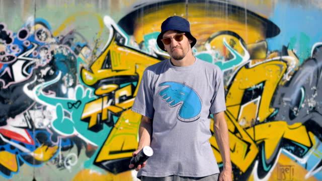 slow motion-film av en gatukonstnär som gungade upp ett fat med färg - väggmålning bildbanksvideor och videomaterial från bakom kulisserna
