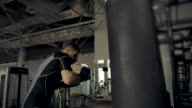 istock Slow motion footage of a young strong tall sportsman punching boxing bag 1274094121