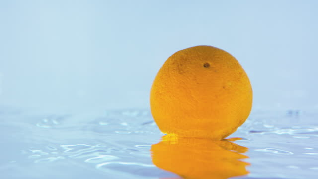 Slow Motion Footage Of An Orange Spinning On Water Surface video