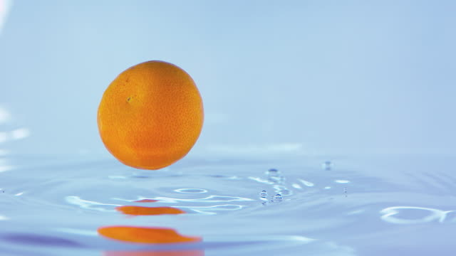 Slow Motion Footage Of An Small Orange Falling On Water Surface video