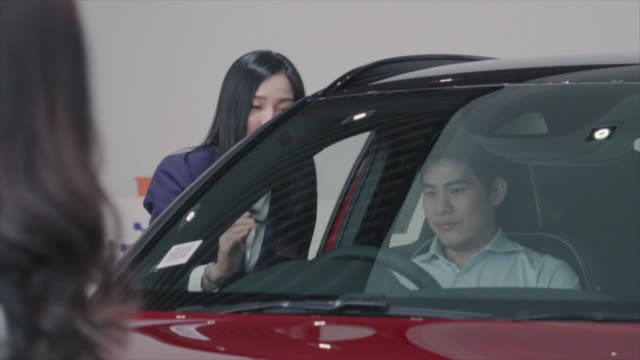 4K Slow motion footage of Asian Saleswoman introducing customer to test drive in showroom