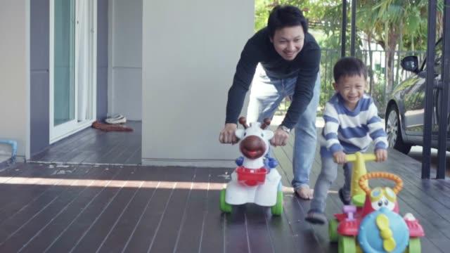 息子とアジアのシングルお父さんの4K スローモーション映像は、自己学習や家庭の学校、家族や子供の頃のコンセプトのために近代的な家の前の芝生でおもちゃの車を一緒に遊んでいます ビデオ