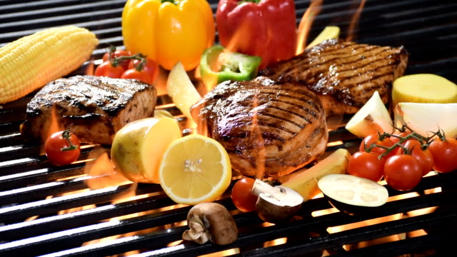Slow motion footage of assorted grilled meat with vegetable on the flaming grill video
