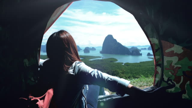 4K Slow motion footage of Attractive Asian woman traveler sitting in tent and looking at view of mountain, feel freedom and enjoy nature at Samed Nang Chee, Travel and Happiness lifestyle concept