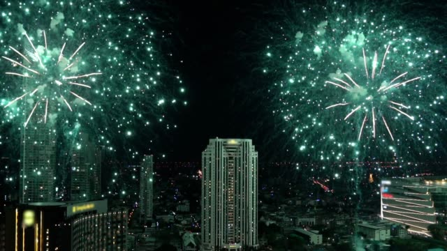 4k slow motion footage of bangkok cityscape with fantastic multicolor firework over night sky at night time, celebration and festival concept - chinese new year filmów i materiałów b-roll