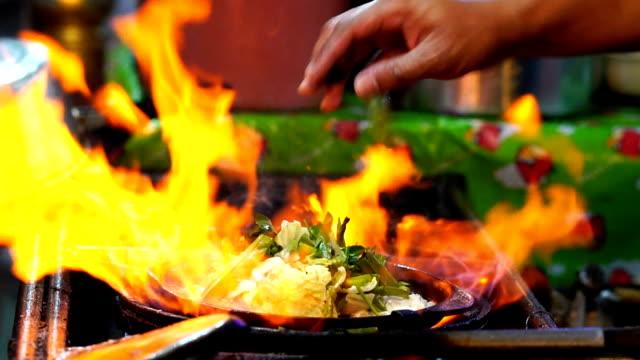 Movimiento lento de FHD imágenes de primer plano cocina Suki salteada por la espada de la sartén sobre el pan, alimento de tradición de Tailandia, comida asiática - vídeo
