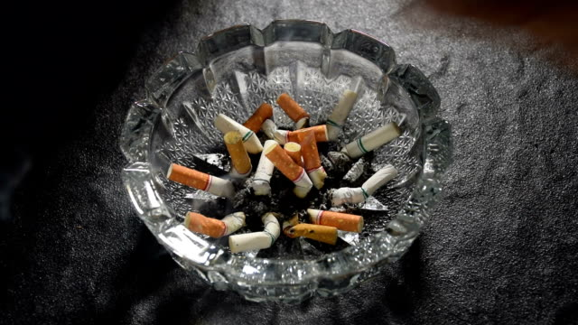 slow motion footage of hand pushing lit cigarette butt in an ashtray - nicotina video stock e b–roll