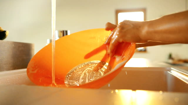 slow motion footage of person rinsing orange bowl under running water from faucet at home - погружённый стоковые видео и кадры b-roll