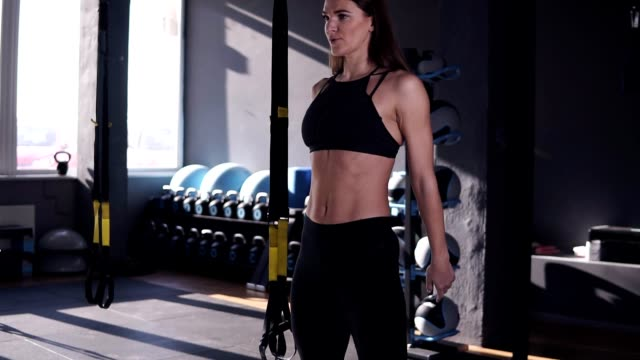 Slow motion footage of professional sportswoman in black sportwear doing exercise for butt muscles and legs. Attractive girl is practicing deep sit ups in modern gym with modern equipment on the background