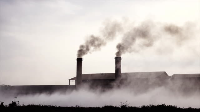 4K Slow motion footage of Smokestack Factory at the countryside at evening time, industry and pollution concept
