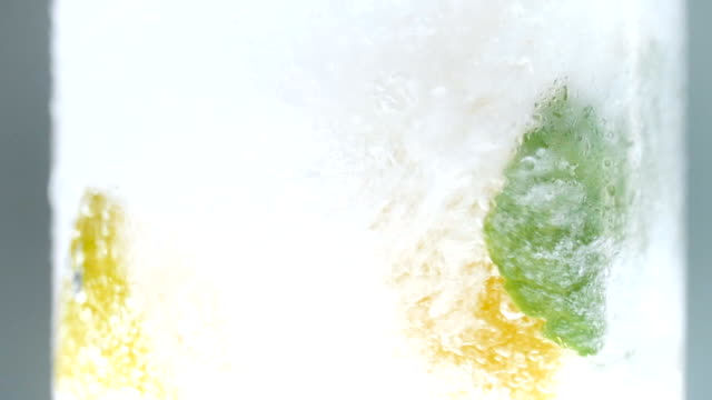 Slow motion footage of soda water slowly pouring in glass with lemons, mint and ice Slow motion video of soda water slowly pouring in glass with lemons, mint and ice carbonated stock videos & royalty-free footage