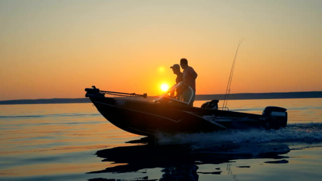 Slow motion footage of two fishermen sailing on a boat. Friendship, best friends concept.