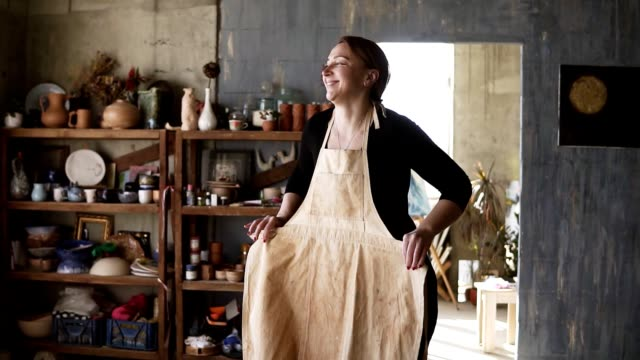 vídeos de stock e filmes b-roll de slow motion footage of young caucasian woman in casual clothes in pottery workshop, with ceramic wares and supplies on shelves and table with tools, putting on beige apron and smiling - avental