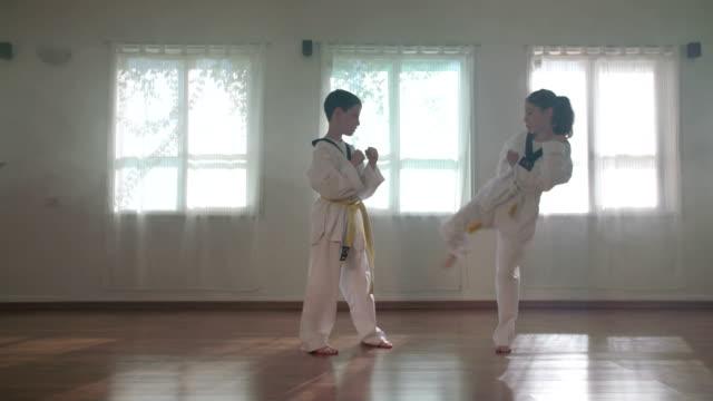 vídeos y material grabado en eventos de stock de cámara lenta imágenes de chicos jóvenes practicando artes marciales - kárate