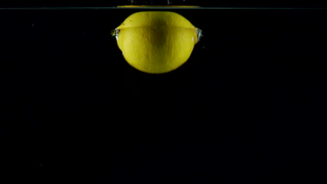 Slow motion fresh lemon falling in the splashes of water on black background video