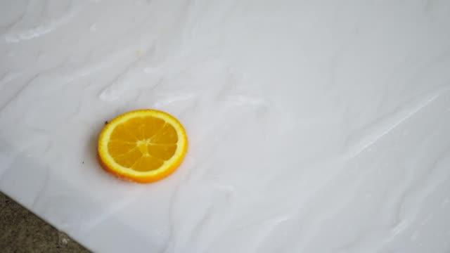 vídeos de stock e filmes b-roll de slow motion fresh orange slice rotating - saladeira