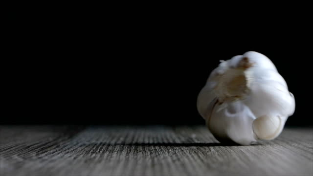 Slow motion Garlic falling on wooden table againts black background video