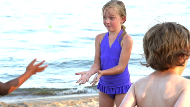 Slow motion Girl catching a water balloon at the beach video