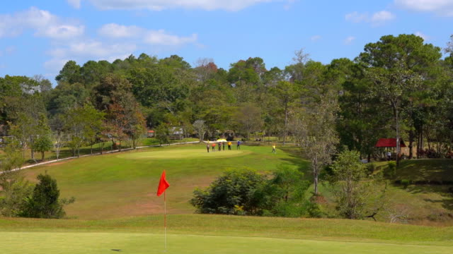 Slow motion golf flag on windy in golf course and beautiful fairway and layout on blue sky and green grass
