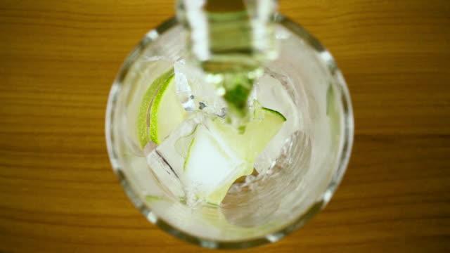 Slow-Motion. Grüne Getränk in ein Glas mit Eis Draufsicht gießen – Video