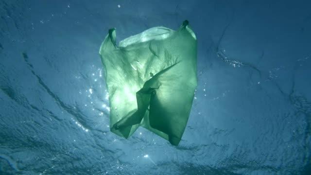 vidéos et rushes de slow motion, sac en plastique vert dérive lentement surface sous-marine dans les rayons du soleil. pollution plastique de l'océan. tir sous-marin, tir à angle bas, contre-jour (rétroéclairage). - en plastique