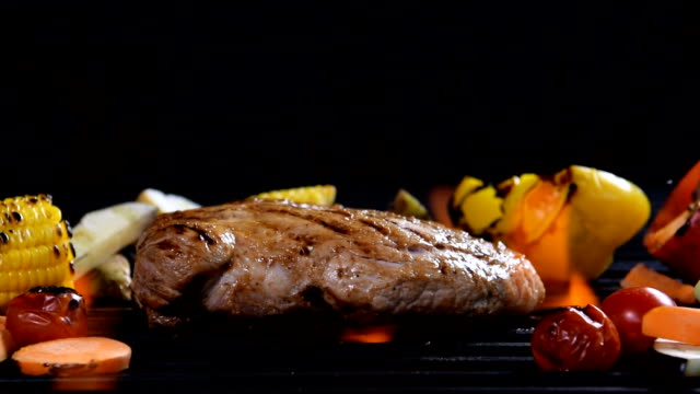 vídeos de stock e filmes b-roll de slow motion - grilled meat /steak with vegetable on a flaming grill - costeleta comida
