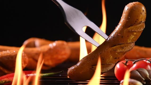 vídeos de stock, filmes e b-roll de slow motion: salsichas grelhadas na grelha flamejante - salsicha